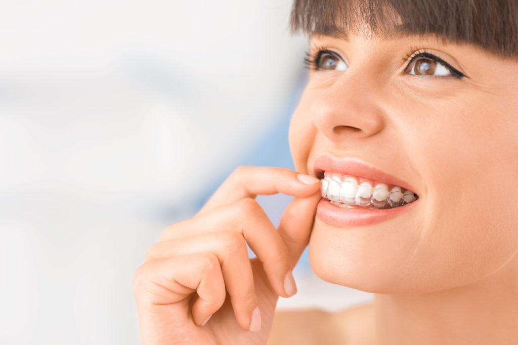 photo of a woman using Invisalign teeth straighteners